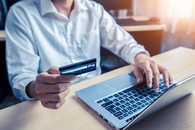 オンラインショッピングにクレジットカードを使用して若い男 Premium写真