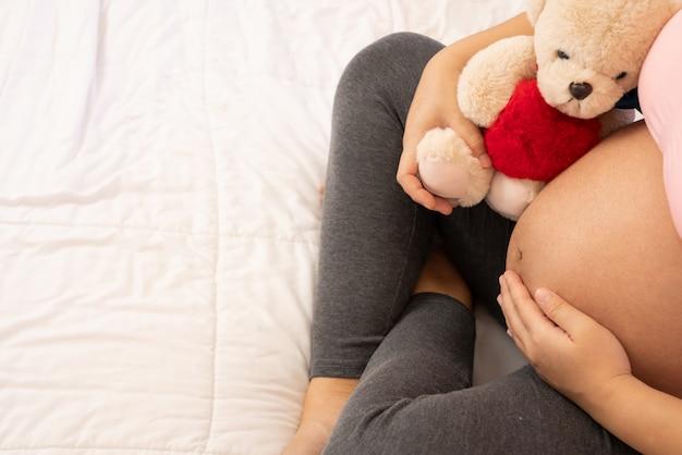 Счастливая беременная женщина и ожидающий ребенок. Premium Фотографии