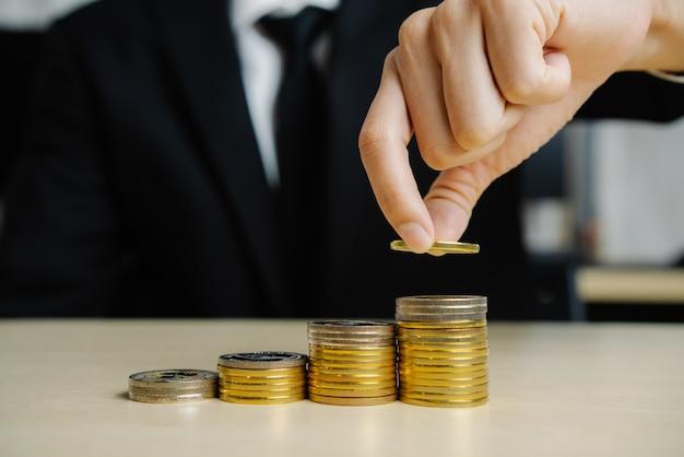 Бизнесмен работая с валютой денег монетки. Premium Фотографии