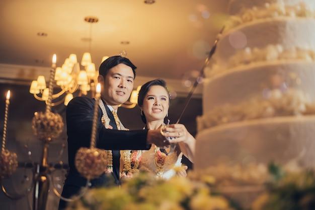 ケーキの前にアジアの結婚式のカップル Premium写真