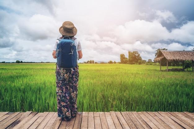 アジアの田んぼの風景をハイキングする女性旅行者。 Premium写真