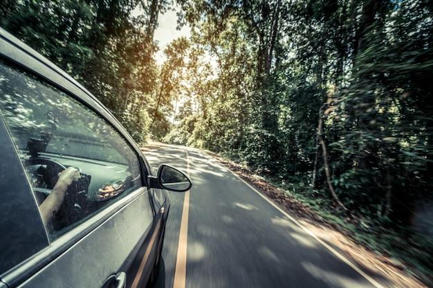 Вид сбоку вождения автомобиля по дороге в лесу шоссе Premium Фотографии