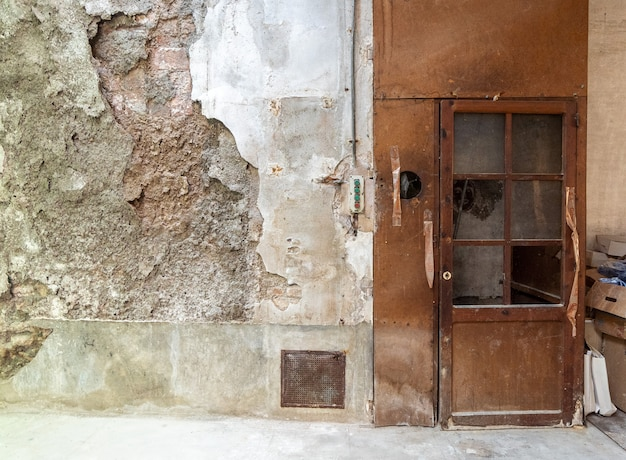 壊れた壁に古いフォークリフトのドア Premium写真