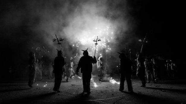 Люди, одетые как дьяволы, празднующие с пиротехникой Premium Фотографии