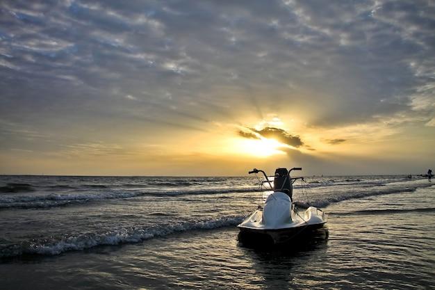 ビーチで光線、雲と白いジェットスキーと夕日の美しい景色。低いキー自然とスポーツのコンセプトです。 Premium写真
