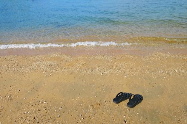 ビーチでの黒いスリッパ Premium写真