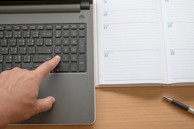 ビジネスの手の拡大は、ノートパソコンのキーボードを指していますラップトップでの作業と整理 Premium写真