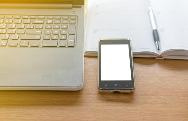 ラップトップスマートフォンと整理のビジネスワーキングテーブル Premium写真