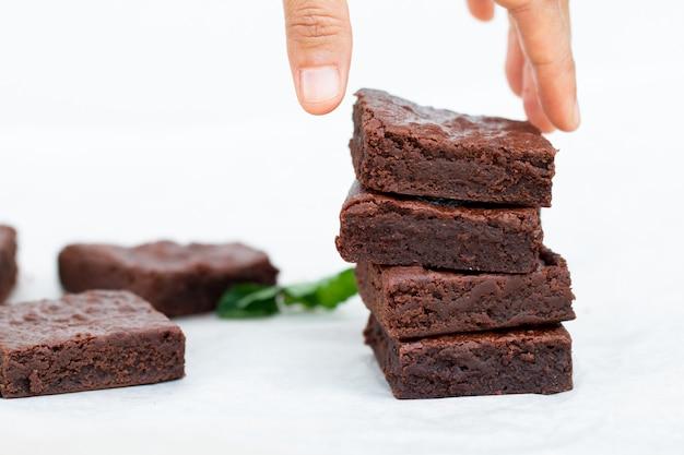 アジアの手がチョコレートブラウニーを選ぶ Premium写真