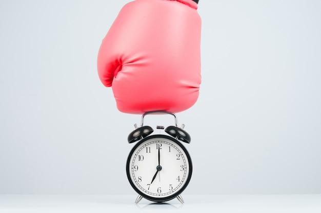 Красные боксерские перчатки, пробивающие классический будильник. Premium Фотографии