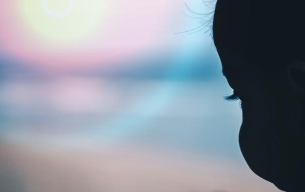 ビーチで遊んでいる子供の顔のシルエットは、ぼやけた背景です。 Premium写真