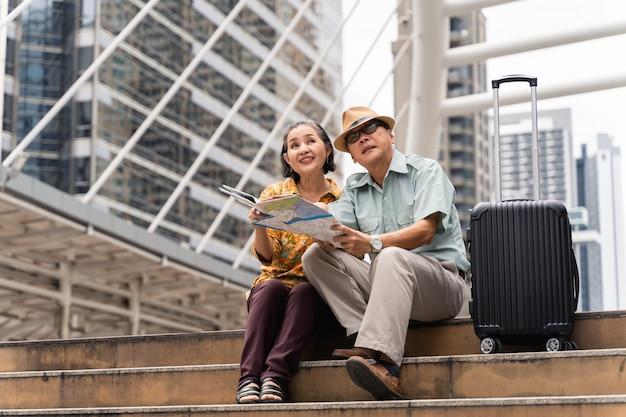 首都を楽しそうに訪れ、楽しんで地図を見て訪問する場所を見つける、アジアの高齢の観光客のカップル。 Premium写真