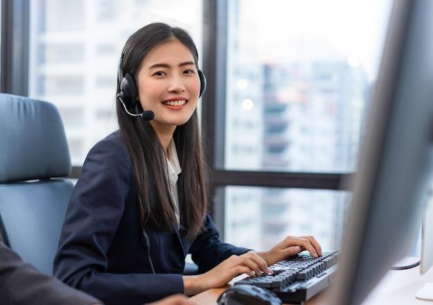 Счастливый улыбающийся оператор азиатских женщина агент по обслуживанию клиентов с гарнитурой Premium Фотографии