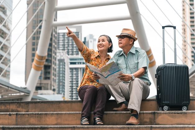 Пара пожилых азиатских туристов, которые с удовольствием посещают столицу, весело проводят время и смотрят на карту, чтобы найти места для посещения. Premium Фотографии
