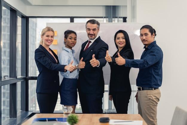 Успешные веселые деловые люди группа многорасовых бизнес команды с большими пальцами руки вверх и улыбаясь позирует Premium Фотографии