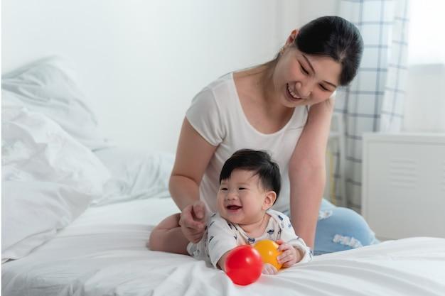 ベッドの上のアジアの赤ちゃんと白いボールの上で一緒におもちゃのボールを遊んで幸せで陽気な気持ちとベッドの上でクロールする赤ちゃんを持つ若い美しいアジアの母。赤ちゃん家族の概念 Premium写真