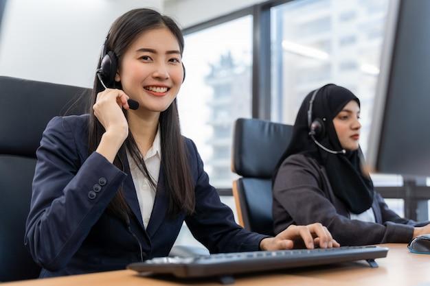Счастливый улыбающийся оператор азиатская женщина клиент службы агент с гарнитурой работает на компьютере в колл-центр, разговаривая с клиентом за помощь в решении проблемы с ее умом обслуживания Premium Фотографии