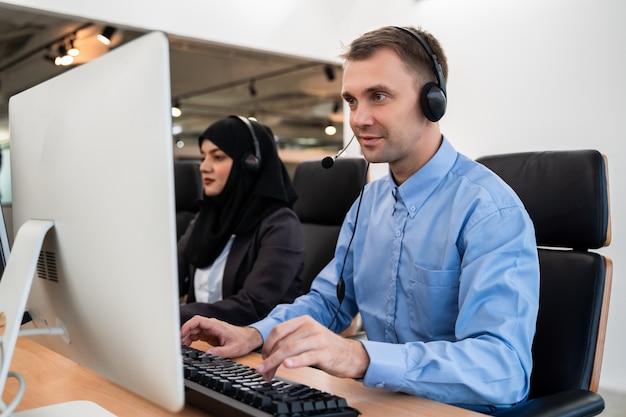 コンピューターで作業して、サービス精神で顧客と話しているヘッドセットを着ているハンサムな若い男性のコールセンターのオペレーター Premium写真