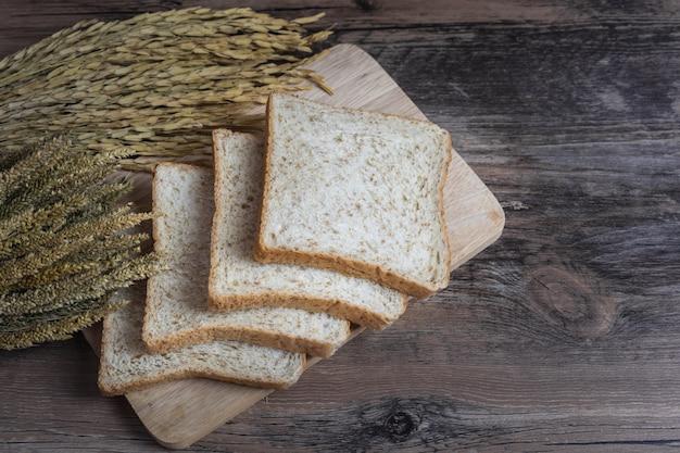 水田の耳と木製のテーブルの全粒粉パンまたは全粒粉パン Premium写真