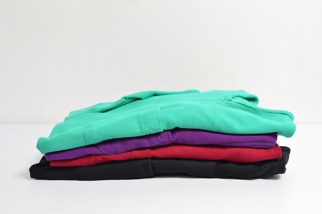 マルチカラーの女性のシャツ、ストライプ、ハンガー、白い背景 Premium写真