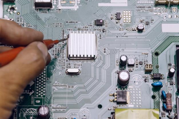 技術者はテレビボードを修理し、エンジニアはテレビボードの電圧を測定します Premium写真