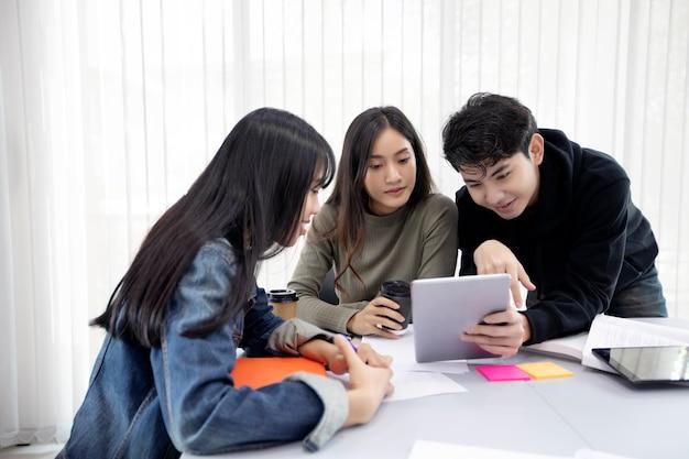 グループの学生笑顔とタブレットを使用することで、仕事やプロジェクトでアイデアを共有することもできます Premium写真