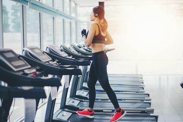 ジムでスポーツ靴を履いているアジアの女性と女性がトレッドミルでジョギングをしています Premium写真