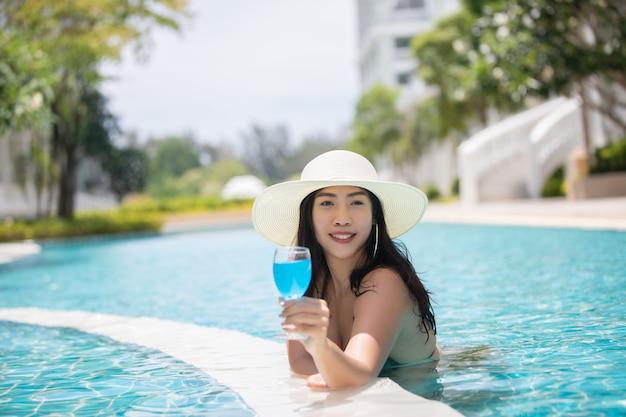 Женщины носят бикини и пьют коктейли жарким летом в бассейне. Premium Фотографии