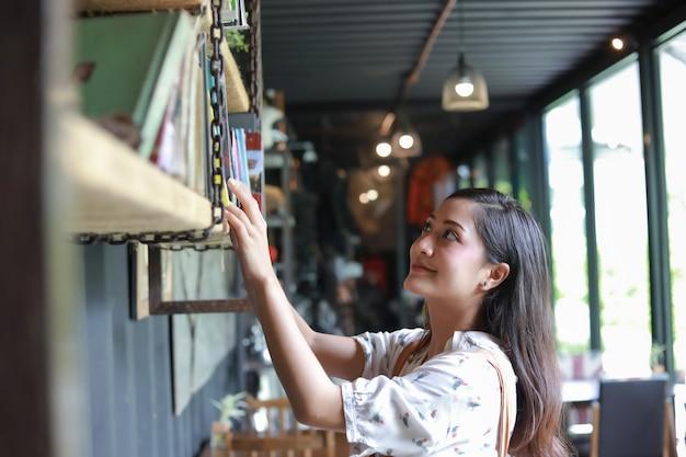 アジアの女性の選択読書と笑顔と幸せのための本喫茶店でリラックス Premium写真