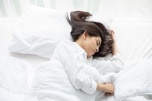 Красивая азиатская женщина греется и спит в белой кровати. Premium Фотографии