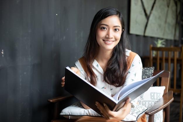 Азиатские женщины читая и усмехаясь и счастливые ослаблять в кофейне после работы в успешном офисе. Premium Фотографии