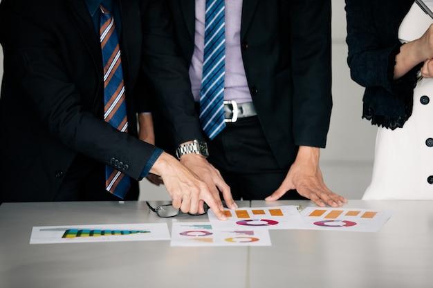 働くビジネスマンとオフィステーブルのグラフ財務図と分析文書上のポイント Premium写真