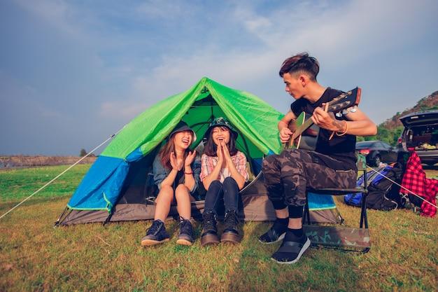 Группа азиатских друзей-туристов, пьющих и играющих на гитаре вместе со счастьем летом во время похода возле озера на закате Premium Фотографии
