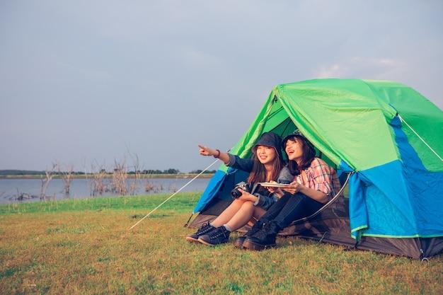 Группа азиатских друзей-туристов, пьющих вместе со счастьем летом во время кемпинга Premium Фотографии