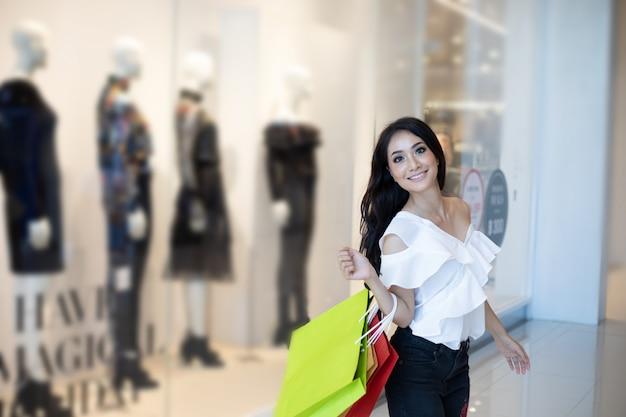 美しい少女は買い物袋を保持しているとスーパー/モールで買い物をしながら笑顔 Premium写真