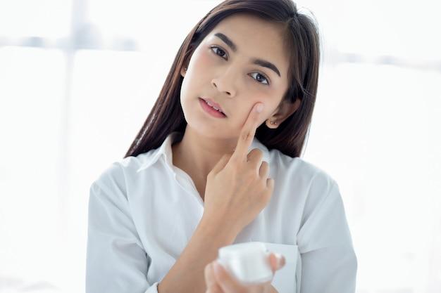 Красивая азиатка с помощью средства по уходу за кожей, увлажняющего крема или лосьона, ухаживающего за ее сухой кожей. увлажняющий крем в женских руках. Premium Фотографии