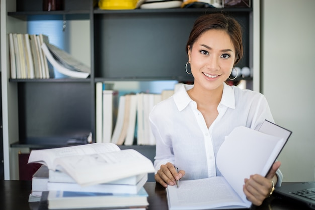 笑顔で本を読んで自宅でアジアの女性学生 Premium写真
