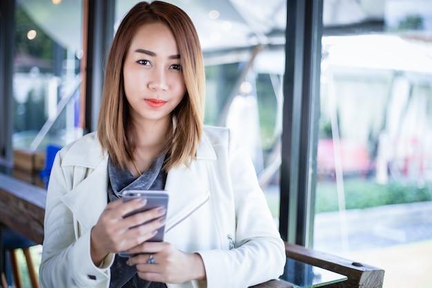 電話を使用してオンラインショッピングと自由な時間の間にコーヒーショップで携帯電話を呼び出すアジアの女性 Premium写真