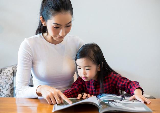 Азиатская мать учит свою дочь читать книгу во время перерыва в семестре на живом столе и дома на холодном молоке. образовательные концепции и деятельность семьи Premium Фотографии