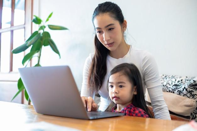 アジアの母親は娘に本を読んだり、自宅で学校の休暇中にオンライン学習用のノートやテクノロジーを使用したりするように教えています。家族の教育概念と活動 Premium写真