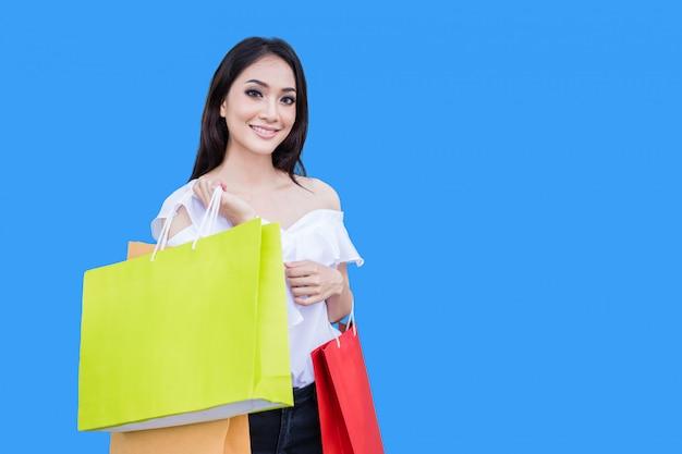 美しいアジアの若い女性は買い物袋を持って立っています。彼女は青色の背景にショッピングモールで幸せを笑顔します。 Premium写真