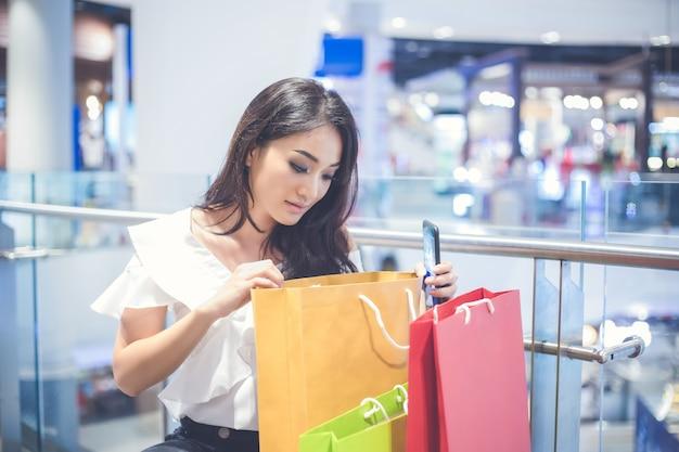 アジアの女性と美人はスーパーマーケット/モールでショッピングバッグを持っています Premium写真