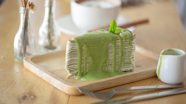 木製のプレートに緑茶の葉と緑茶クレープケーキ。 Premium写真