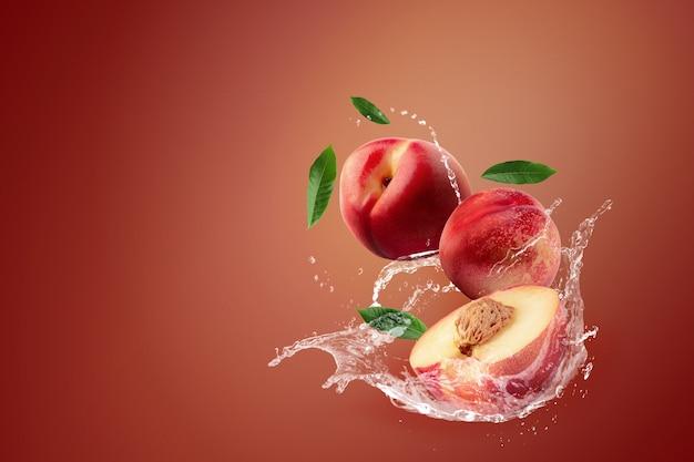 赤の背景に新鮮なネクタリンの果実にはねかける水。 Premium写真