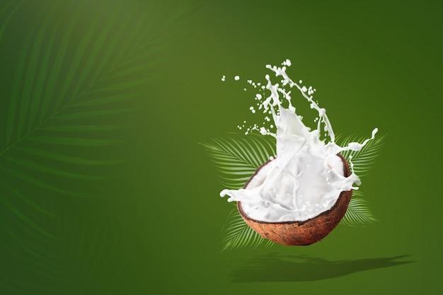 Брызги кокосового молока на зеленом фоне Premium Фотографии