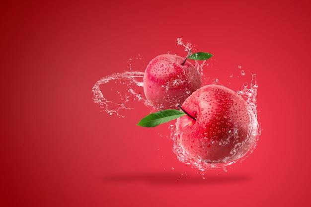 赤の背景に新鮮な赤いリンゴにはねかける水。 Premium写真