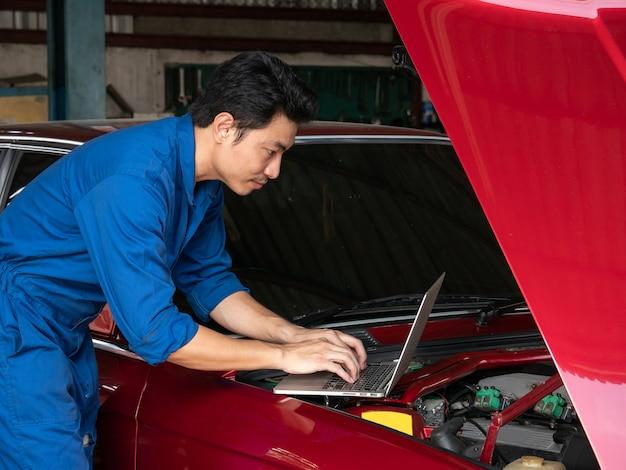 ラップトップコンピューターを使用して車のエンジンをチェックし、修理ガレージで親指を現してハンサムなアジアのメカニック。 Premium写真