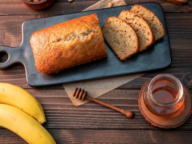 カシューナッツと木製のテーブルの上に蜂蜜とスライスした自家製バナナパンポンド。 Premium写真