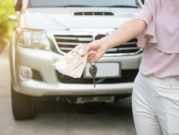 Закройте вверх руки держа ключ денег и автомобиля против автомобиля. страхование, кредит и финансы Premium Фотографии