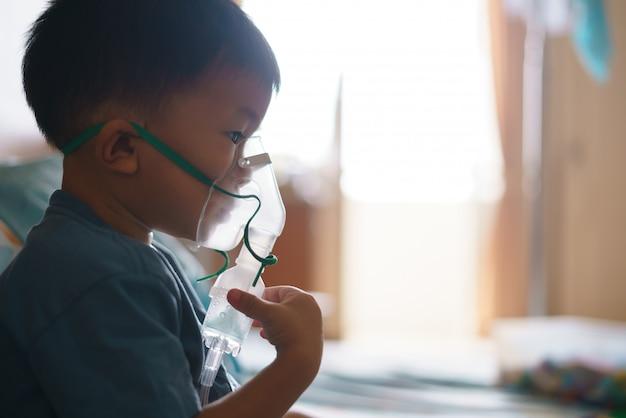咳を止めるために薬を含む吸入器を使用しているアジアの少年 Premium写真